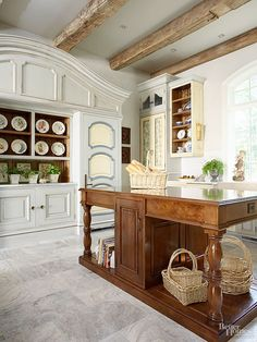 Massive breakfront cabinetry sets the kitchen's blue, gray, and buttery yellow scheme, enhanced by bright white trim, a subway tile backsplash, and marble countertops. The hutchlike storage and stained wood island bring furnished-room appeal to the efficient work space.
