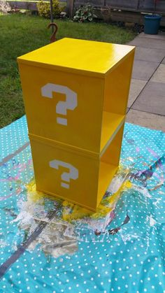 Mario question block shelves! Stuck two old pine beside cubes together with No More Nails, painted with white undercoat twice, made a question mark stencil from paper, backed with double-sided tape and sprayed yellow. Great results! | DIY geek home decor ikea