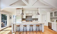 The kitchen hosts a vaulted ceiling with exposed trusses, white cabinetry and subway tile backsplash. Photo: Lupine Hammack / ONLINE_CHECK