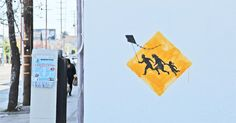 """Street Artist Bansky transforms """"immigrant crossing"""" sign. Let's remember that """"immigrant"""" describes people not a problem."""