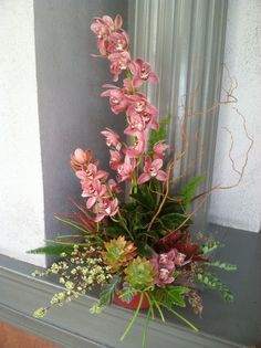 Towering cymbidiums stand out among succulents and cut foliage. Flower Fabulous by HM Florals and Crafts