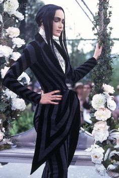 * John Galliano for Dior Belle Epoque inspired Fall/Winter 1997-1998 Model  wearing a black velvet and blue wool striped skirt suit with extended V-peplum on jacket, white high-necked blouse, and elaborate rhinestone bib necklace. Circa September 1996 © Guy Marineau