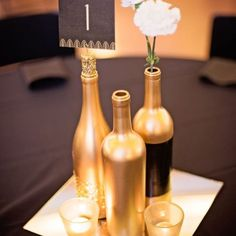 Gold and glitter wine bottles as the table centerpieces for weddings or corporate event. Black and gold Great Gatsby style table cards with white carnations, gold mirror plates and gold glitter votive (Gold Bottle Centerpieces) Great Gatsby Wedding, Gold Wedding, Floral Wedding, Diy Wedding, Trendy Wedding, Wedding Ideas, Wedding Themes, Gatsby Party, Wedding Flowers