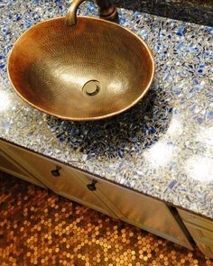 A hammered copper sink and Vetrazzo counter complement the floor of pennies in the bathroom of New Braunfels resident Doreen Fisher. Photo: Tracy Hobson Lehmann / SA