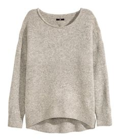 Soft knit sweater with wool content. Rolled-edge neckline, long sleeves with dropped shoulders, and rounded hem. Slightly longer at back.