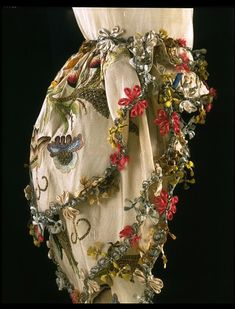 Finely petalled rosettes punctuate the fly fringe (braid) adorning this 1760s sack-back gown. They are made of narrow strips of parchment, covered in silk and twisted into the shape of petals, a technique used in both embroidery and lace since the late 17th century. In addition to the rosettes, the fringe incorporates loops of silver thread with tufts of coloured floss silk. Known as fly fringe, these knotted and highly decorative trims were a popular embellishment for women's dress between…