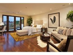 Natural wooden floors & gorgeous pops of cream and white decor make this bedroom feel cozy and warm.