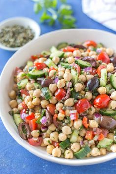 Mediterranean inspired chickpea salad with olives cucumber tomatoes onion in a white bowl on a blue background sitting next to a small bowl of capers a parsley sprig and a white and red striped kitchen towel. Greek Chickpea Salad, Mediterranean Chickpea Salad, Mediterranean Diet Recipes, Quinoa Salad, Mediterranean Style, Chic Pea Salad, Healthy Salads, Healthy Recipes, Side Dishes