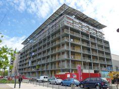 Amplia, Quartier de La Confluence, Lyon  Ce projet résidentiel  à « énergie positive » vise à réduire au maximum l'usage de ressources naturelles.  Les appartements le constituant sont de type traversant. C'est une technique architecturale qui permet un accès optimal à la lumière du jour.  Une toiture photovoltaïque fait également office de brise-soleil, pour protéger les façades et les terrasses de l'ensoleillement et améliorer le confort en été.  Crédit : alex690071 sur Flickr ©