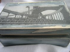 Drewniana, postarzana szkatułka z aplikacją Mostu Grunwaldzkiego, nakładaną techniką decoupage.