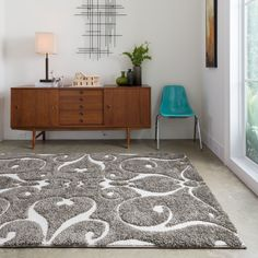 Add the finishing touch to a room with this contemporary shag rug. The durable polypropylene rug features a one-inch pile in varying heights, and an abstract design in charcoal gray, brown, and ivory which will flatter almost any room.