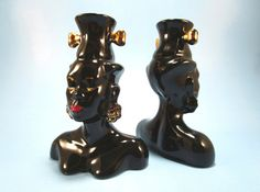 This fantastic pair of 1950s Nubian Blackamoor head vases, painted a glossy jet black with metallic gold and red accents, would make a