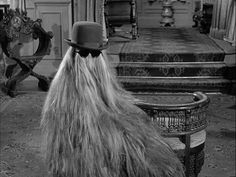"""Cousin Itt -- Itt Addams is the cousin of Gomez Addams. He is a short being whose entire body is shrouded by long hair. When Gomez asks Cousin Itt what is underneath all the hair, Cousin Itt replies, """"Roots"""". The Addams Family 1964, Addams Family Tv Show, Cousin It Adams Family, Los Addams, Charles Addams, Best Hair Straightener, Weekend Events, The Munsters, Kids Laughing"""