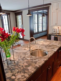Dark wood trim, dark island and lower cabinets, light upper cabinets