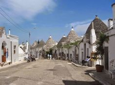 """Alberobello — A small town and commune in the province of Bari, in Puglia, Italy. The town is located on two hills divided by the river. On the east stands the modern Alberobello, and on the west - famous for its unique med-evals buildings Trullo, They take their name from the Latin world """" Trulla"""" which means dome. Original structures called """" Trulli"""" of Alberobello give unique uniqueness. These unusual white houses with conical roofs from the whole street."""
