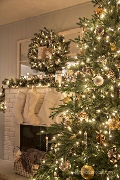 Christmas tree at night - I very much love the wall paneling, brick fireplace, and wire basket, even more than the beautiful decorations