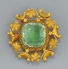An early 19th century gold and Aquamarine brooch The central cushion shaped mixed-cut aquamarine in gold claw mount with engraved foliate and scroll border circa 1840