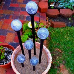 "DIY Outdoor Lighting. I used Solar Powered lights purchased from Walmart and put them on 1/2"" PVC pipe that I primed and spray painted to match the metal casing on the light fixtures. Fill a pot with sand and stagger your lights!"