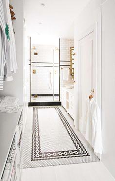Baño con vestidor integrado moderno en blanco y bronce, con azulejos tipo subway y piso de mini azulejos hexagonales con guarda negra. En una casa a puro blanco con acentos de color.