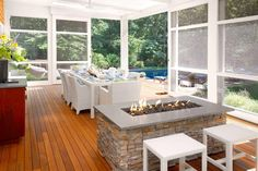 This stunning, contemporary sun room boasts sliding glass walls that open up to a sunny pool deck, blurring the line between indoor and outdoor living space. A long, bright white dining table offers tons of space to entertain while a stone fire pit creates a cozy mood on cool nights.