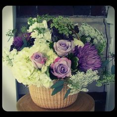 """Natucket basket filled with purple mums, white hydrangea, """"Purple Haze"""" roses, Queen Anne's Lace, stock and dark sedum.  Roberts Flowers of Hanover, Hanover, NH"""