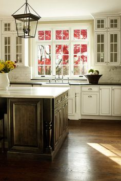 Elegant kitchen - stained wood island, white cabinets, carrara marble island & backsplash