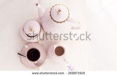 Coffee service in elegant  pink porcelain with gold on the border. - stock photo