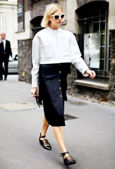 A white cropped longsleeve top is worn with a black midi skirt, statement sunglasses, and strappy black flats