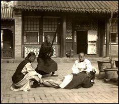 A MAN GETTNG PUNISHED FOR BEING A WIFE BEATER -- Justice in a Domestic Violence Case in OLD CHINA Ca.1900 image by an unknown photographer working for the H.C. White Stereoview Company of Vermont, USA.