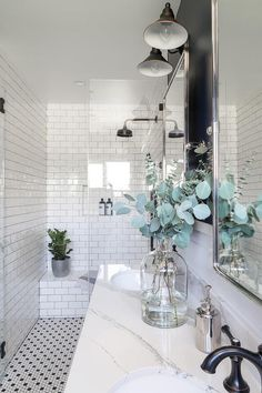 Black vintage barn sconces light a navy blue and white bathroom featuring rectangular pivot mirrors hung from a blue upper wall lined with a white shiplap trim.