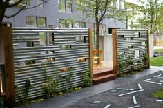 corrugated steel fence with playful cut outs by fanny