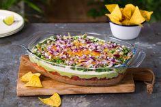 Deilig dipp i syv lag med blant annet bønnemos, rømme, ost og tomat, gratinert i ovnen og klar til å nytes med sprø tortillachips. Bedre enn dette blir ikke en vegetarisk 7 layer taco dip.