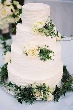 simple romantic white buttercream wedding cake with roses and greenery