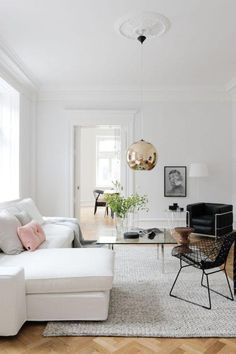 Chic, minimalist family living room with a white sectional sofa, white area rug, black wire arm chair, pink velvet pillow and dramatic brass gold pendant light. Love!