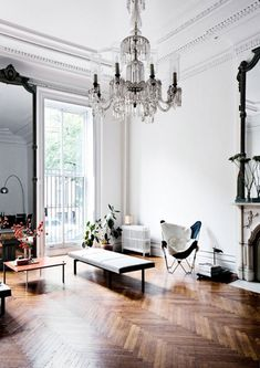 Beautifully elegant living room — a wonderfully rich looking home with white minimal walls and fine accessories / herringbone-floor-crystal-chandelier