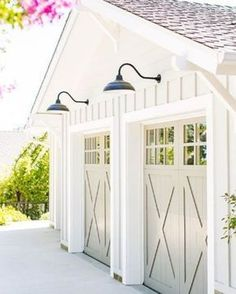 These carriage house garage doors add a soft gray tone to a white garage. Notice the garage door windows, x braces, molding and goose neck lights for the total package!   25 Gorgeous Garage Doors