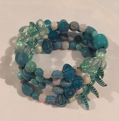 Dark Green, Clear, Off White, Light Green, Dark Blue, Dark Grey, and Blue Green Medium Memory Wire Bracelet. Please visit my facebook page called The Pelican By Kristin Margarite. https://www.facebook.com/ThePelicanbyKristin/?ref=aymt_homepage_pane