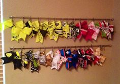 Cheer bow holder to finally put an end to the bow craziness!  So simple...just curtain rods and curtain clips.