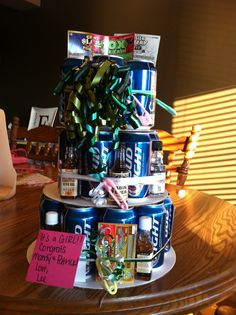 """Beer cake! Great gift idea!!   I used 1 each of an 8"""", 10"""", & 12"""" cardboard circles (found in 6 packs of each size at Walmart), 29 beers, 7 Lotto scratch offs, 5 mini shots, 1 pkg plastic safety pins (found for $1 at dollar tree), & curling ribbon.   Place the beers in a circle on the cardboard & tie tight w ribbon, stack & repeat twice. Then slide in shots & lotto tickets. On some of the ribbon I tied the baby pins to them, and the rest of the pins I just slid in the cracks between the…"""