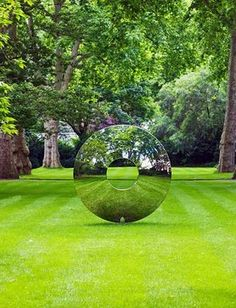 This amazing piece of contemporary sculpture by David Harper naturally draws the eye in. The light and reflections from the polished stainless steel create lovely effects in the garden.