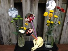 Photo Sticks made with Target dollar bin paper straws and clothespin's for mom's celebration service. Mini pom flowers in small vases and jars.  Each table will have a photo gourd and a photo vase.