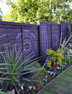 Purple fence hand painted with henna-inspired designs and spiky planting from phormiums and cordylines