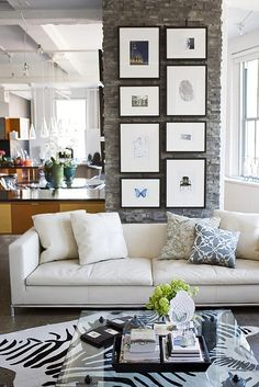 modern eclectic gallery wall on a narrow brick wall of modern and vintage prints - Gallery Wall Ideas