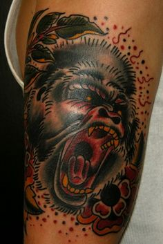 Old school color-ink gorilla with flowers tattoo on upper arm ...