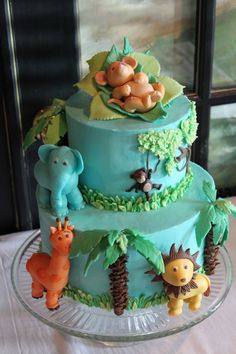 This two tier cake was inspired by the invitation & the nursery lamp. It is frosted with buttercream. The figurines are made from a gumpaste/fondant mixture. The tree trunk, blades of grass, monkey, & vine are made from fondant. The leaves on the tree are piped with buttercream
