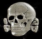"""The """"Death's Head"""" insignia worn by the schutzstaffel, aka """"protection squadron."""" It was a paramilitary organization in WWII.  Part of the Nazi Party, commonly known as the """"SS.""""  Today, I started reading """"The Odessa File,"""" an early 1970's historical novel. Watch for my review later this summer."""