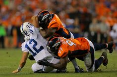 Defensive end DeMarcus Ware #94 of the Denver Broncos and defensive end Malik Jackson #97 of the Denver Broncos combine to sack quarterback Andrew Luck #12 of the Indianapolis Colts in the second quarter of a game at Sports Authority Field at Mile High on September 7, 2014 in Denver, Colorado.