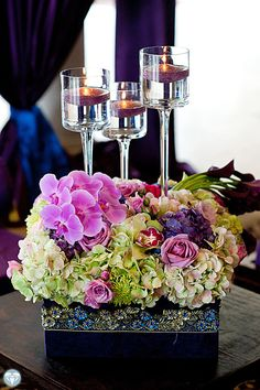 Wedding centerpiece idea.  Green Hydrangeas with purple orchids and tall floating candles.  Lovely!