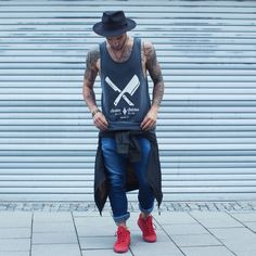 Streetstyle : Barber and Butcher Tanktop in Vintage black, Red Son of Blades Premium Sneakers with DP Bomber Jacket in Army Green around the waist in combination with a hat & blue denim jeans