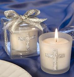 """Looking for christening, first communion or confirmation favors, or classic gifts that are appropriate for any religious occasion? These Fashioncraft-exclusive candles make a perfect choice! Each 2"""" x 1 3/4"""" favor features a sturdy white frosted glass holder decorated with a sparkling silver cross design, with a white poured candle inside. Packaged with punch, these candles come ready for dramatic presentation inside a deluxe clear box topped with a sparkling silver bow."""
